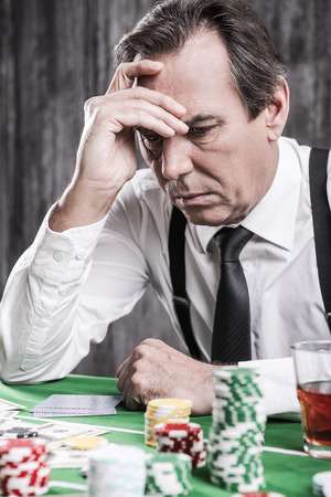 Bad luck. Depressed senior man in shirt and suspenders holding head in hand while sitting at the poker table with money and gambling chips laying all around him