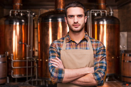Foto de Confident brewer. Confident young male brewer in apron keeping arms crossed and looking at camera while standing in front of metal containers - Imagen libre de derechos