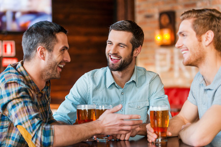 Foto de Meeting with the best friends. Three happy young men in casual wear talking and drinking beer while sitting in bar together - Imagen libre de derechos