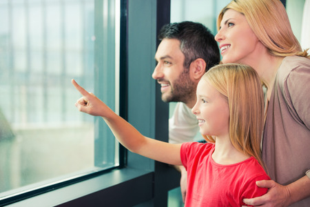 Photo for Is it a plane? Happy family of three bonding to each other and smiling while looking through a window together - Royalty Free Image