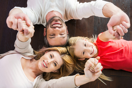 Photo pour Happy family together. Top view of happy family of three bonding to each other and smiling while lying on the hardwood floor - image libre de droit