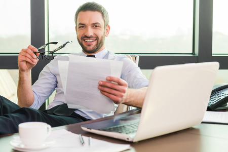 Photo for How may I help you? Handsome mature man in shirt and tie adjusting his eyeglasses and smiling while sitting at his working place - Royalty Free Image