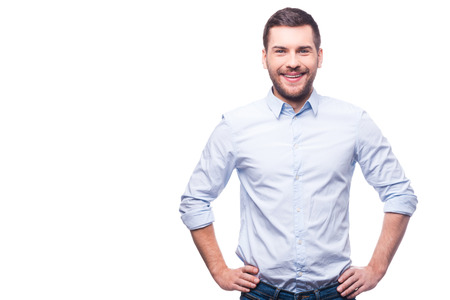 Photo pour Handsome young man in shirt looking at camera and holding hands on hips while standing against white background - image libre de droit