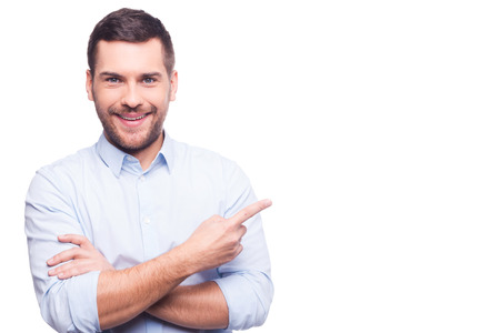 Foto de Businessman pointing copy space. Handsome young man in shirt looking at camera and pointing away while standing against white background - Imagen libre de derechos