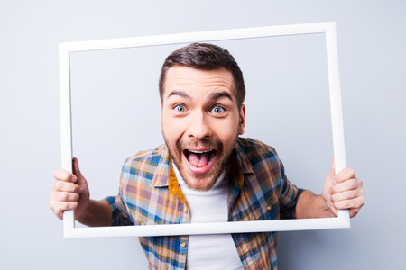 Foto de Handsome young man in shirt holding picture frame in front of his face and smiling while standing against grey background - Imagen libre de derechos