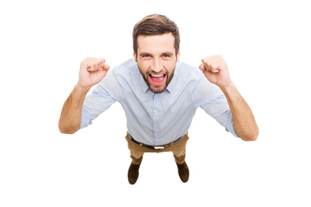 Foto de Everyday winner. Top view of happy young man expressing positivity and gesturing while standing isolated on white background - Imagen libre de derechos