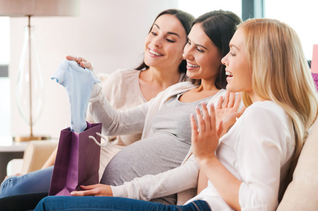 Photo pour Presents for young mother. Happy young pregnant woman receiving gifts from her friends on baby shower party - image libre de droit
