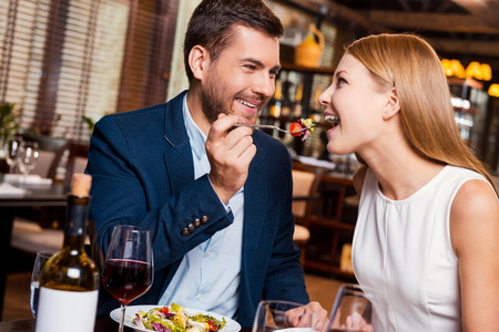 Photo pour Try this! Beautiful young loving couple enjoying dinner at the restaurant while man feeding his girlfriend with salad - image libre de droit