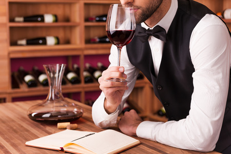 Foto de Sommelier examining wine. Cropped image of confident male sommelier examining wine while smelling it and leaning at the wooden table with wine shelf in the background - Imagen libre de derechos