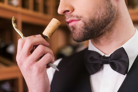 Foto de Enjoying the best wine. Close-up of confident young man in waistcoat and bow tie smelling wine cork - Imagen libre de derechos