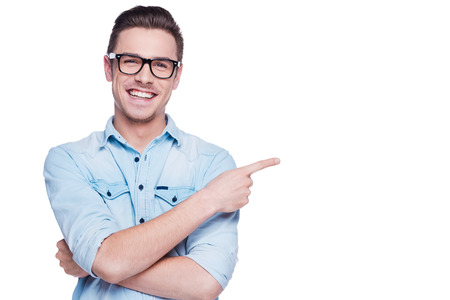 Photo pour Cheerful young man pointing copy space. Handsome young man in shirt looking at camera and pointing away while standing against white background - image libre de droit