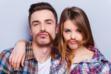 Foto de Funny moustache. Beautiful young loving couple making fake moustache from hair while standing against grey background - Imagen libre de derechos