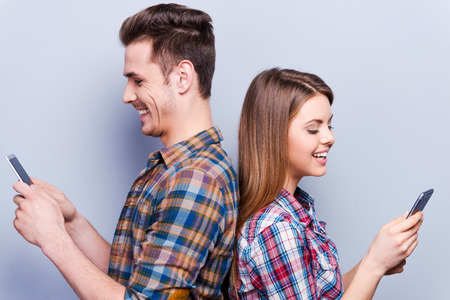 Photo pour Romantic messages.  Beautiful young loving couple holding mobile phones and standing back to back against grey background - image libre de droit