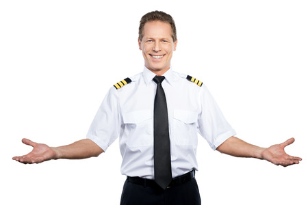 Photo pour Welcome on board! Happy male pilot in uniform gesturing and smiling while standing against white background - image libre de droit