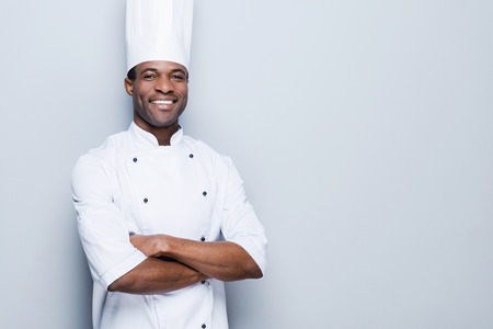 Photo pour Cooking is my passion. Confident young African chef in white uniform keeping arms crossed and smiling while standing against grey background - image libre de droit