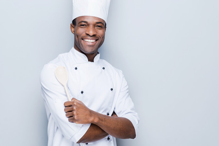 Foto de Confident chef. Cheerful young African chef in white uniform keeping arms crossed and smiling while standing against grey background - Imagen libre de derechos