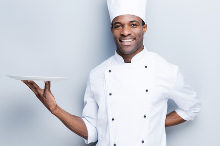 Foto de Copy space at his plate. Confident young African chef in white uniform holding empty plate and smiling while standing against grey background - Imagen libre de derechos