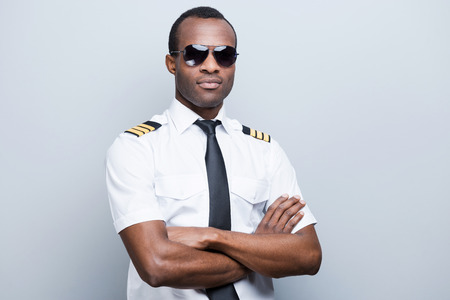 Photo pour Confident and experienced pilot. Confident African pilot in uniform keeping arms crossed while standing against grey background - image libre de droit