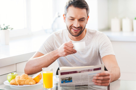 Foto de Starting day from good news. Handsome young man reading newspaper and smiling while drinking coffee and having breakfast in the kitchen - Imagen libre de derechos