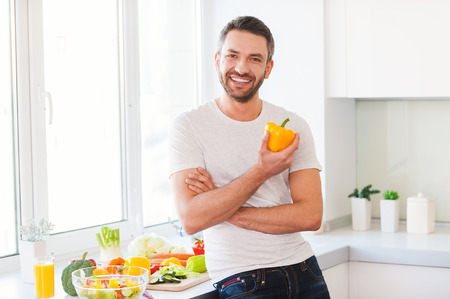 Foto de Healthy food is healthy life. Handsome young man holding fresh yellow pepper and smiling while standing in the kitchen - Imagen libre de derechos