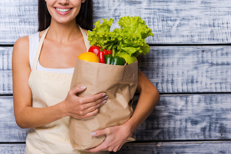 Photo pour Carrying a healthy bag. Cropped image of beautiful young woman in apron holding paper shopping bag full of fresh vegetables and smiling while standing in front of wooden background - image libre de droit