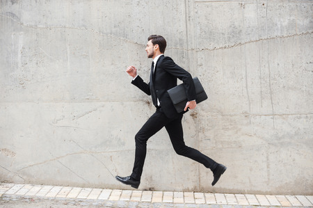Photo pour Hurrying to the new goals. Happy young man in formalwear holding briefcase while running in front of the concrete wall - image libre de droit