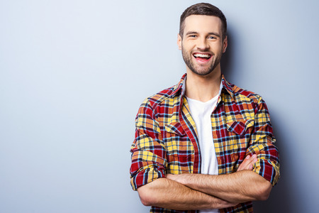 Foto de Happy young man. Portrait of handsome young man in casual shirt keeping arms crossed and smiling while standing against grey background - Imagen libre de derechos