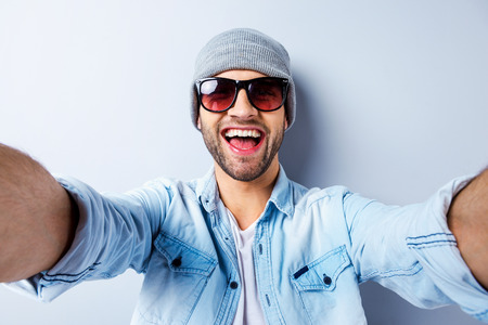 Photo pour Just me and no one else. Top view of handsome young man in hat and sunglasses making selfie and smiling while standing against grey background - image libre de droit