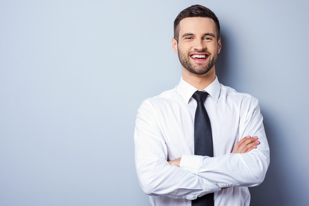 Foto de Young and successful. Portrait of handsome young man in shirt and tie keeping arms crossed and smiling while standing against grey background - Imagen libre de derechos