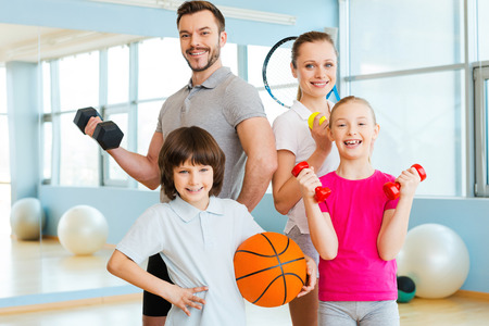 Photo pour Happy and sporty. Happy family holding different sports equipment while standing close to each other in health club - image libre de droit