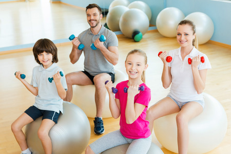 Foto de Enjoying time in sorts club. Top view of happy sporty family exercising with dumbbells in sports club while sitting on the fitness balls together - Imagen libre de derechos