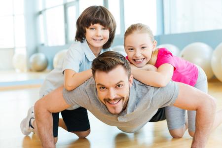 Foto de Exercising with father. Happy little children bonding to their father doing push-ups in sports club - Imagen libre de derechos