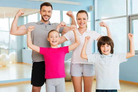 Foto de Proud to be strong and healthy. Happy sporty family showing their biceps and smiling while standing close to each other in sports club - Imagen libre de derechos
