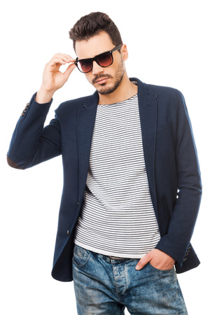 Photo for Confident in his style. Handsome young man adjusting his sunglasses while standing against white background - Royalty Free Image