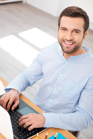Photo for Taking care of business with smile. Top view of handsome young man in shirt working on laptop and smiling at camera while sitting at his working place - Royalty Free Image