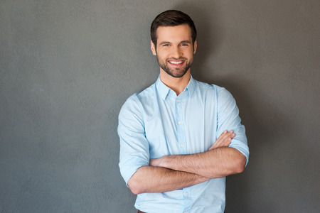 Photo for Handsome and confident. Handsome young man in shirt keeping arms crossed and smiling at camera while standing against grey background - Royalty Free Image