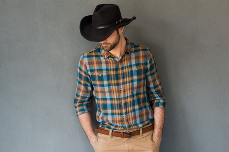 Foto de Cowboy couture. Portrait of young man wearing cowboy hat and looking down while standing against grey background - Imagen libre de derechos