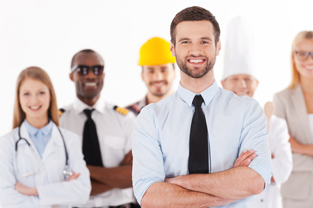 Photo for When I grow up I will be a businessman. Confident young man in shirt and tie keeping arms crossed and smiling while group of people in different professions standing in the background - Royalty Free Image