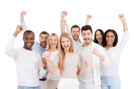 Foto de Successful team. Group of happy young people in smart casual wear looking at camera and keeping arms raised while standing against white background - Imagen libre de derechos
