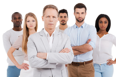 Photo pour Leading his team to success. Confident mature man in smart casual wear keeping arms crossed and looking at camera while group of young people standing behind him and against white background - image libre de droit
