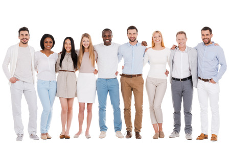 Foto per The best team ever. Full length of happy diverse group of people bonding to each other and smiling while standing against white background together - Immagine Royalty Free