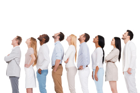 Photo for What is that? Side view of positive diverse group of people in smart casual wear looking up while standing in a row and against white background - Royalty Free Image