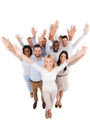 Photo for Dream team. Top view of positive diverse group of people in smart casual wear looking at camera and stretching out their hands while standing close to each other - Royalty Free Image