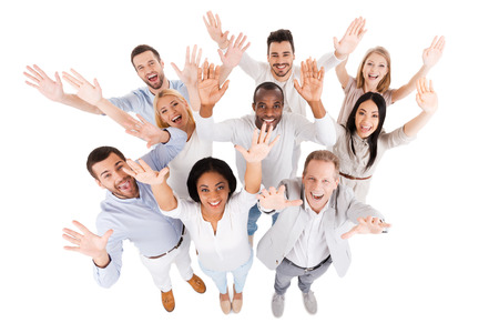 Foto de Successful business team. Top view of positive diverse group of people in smart casual wear looking at camera and stretching out their hands while standing close to each other - Imagen libre de derechos
