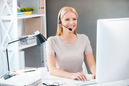 Photo pour Customer service representative at work. Beautiful young woman in headset working at the computer and smiling while sitting at her working place in office - image libre de droit