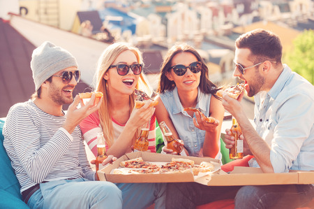 Foto de Friends and pizza. Four young cheerful people eating pizza and drinking beer while sitting at the bean bags on the roof of the building - Imagen libre de derechos