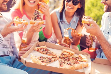 Photo pour Pizza time! Close-up of four young cheerful people eating pizza and drinking beer outdoors - image libre de droit