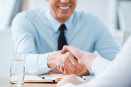 Photo for Sealing a deal. Close-up of two business people shaking hands while sitting at the working place - Royalty Free Image