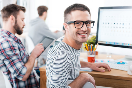 Photo for We keep it casual in our office. Happy young man looking over shoulder and smiling while sitting at desk with his colleagues working in the background - Royalty Free Image