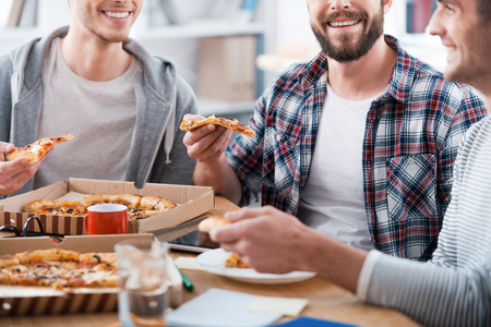Photo for Pizza for productive work. Cropped image of three happy young men eating pizza while sitting at the desk together - Royalty Free Image